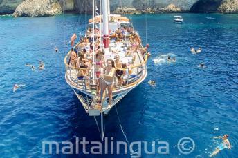 Uczniowie języka angielskiego skaczący do wody z łodzi na Malcie
