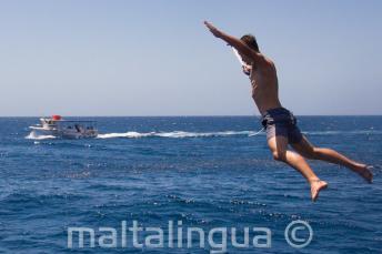Uczeń robiący gwiazdę skacząc z łodzi