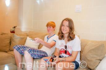 Uczniowie siedzący na kanapie u rodziny goszczącej