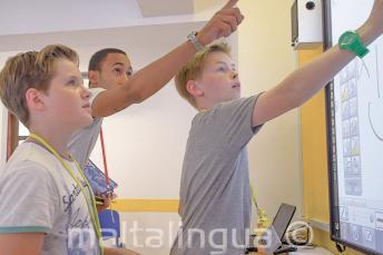 Nauczyciel pomagający 2 ucznią przy tablicy interaktywnej