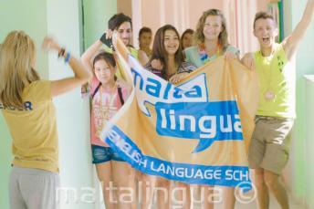 Grupa uczniów języka angielskiego z flagą