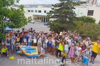 Grupa uczniów przed budynkiem szkoły
