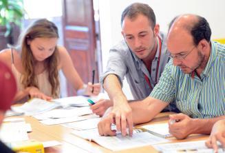 Nauczyciel języka angielskiego tłumaczy coś kursantom w klasie.