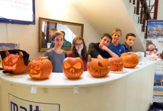 Młodzi kursanci z wyrzeźbionmi dyniami na Halloween w recepcji szkoły