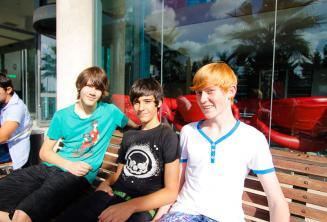 Trzech studentów siedzących przed rezydencją szkolną