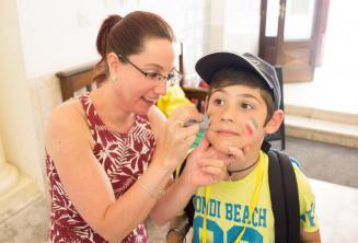 A staff member putting face-paint on a child