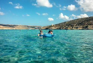Studenci szkoły językowej pływają w wodach Blue Lagoon na Comino